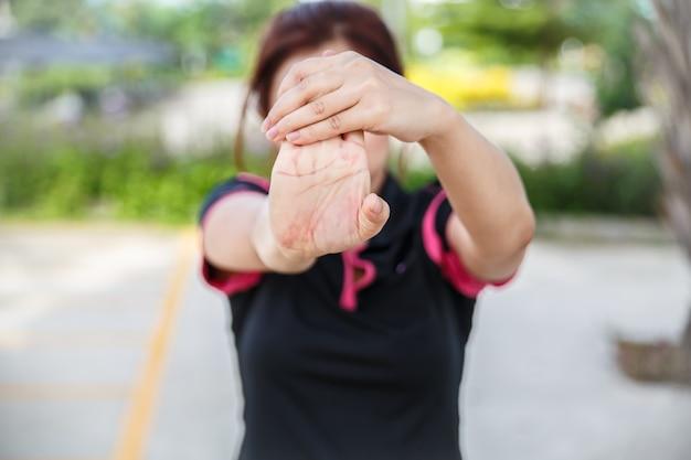運動する女性。彼の手、手首、前腕を伸ばして女性のクローズアップ。