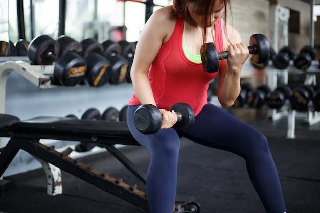 フィットネスジムで運動する脂肪フィットネス女性。運動のコンセプト。