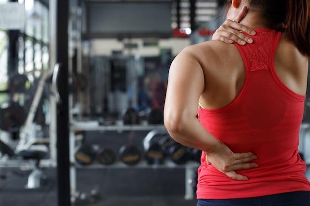 ジムバックグラウンドで女性の身体のマッサージ。ヘルスケアと運動の概念。