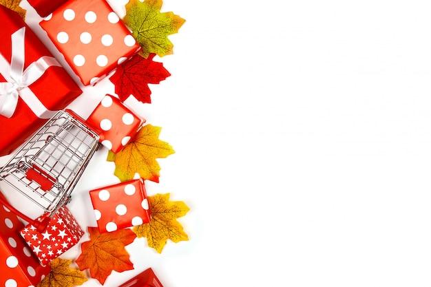 Рамка из кленовых листьев и подарочных коробок на белом фоне