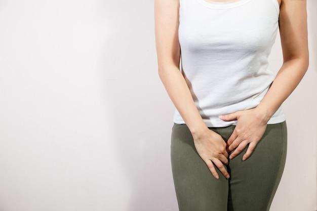 Молодая женщина, имеющая болезненные боли в животе с руки, держа нажатие ее промежность нижней части живота.
