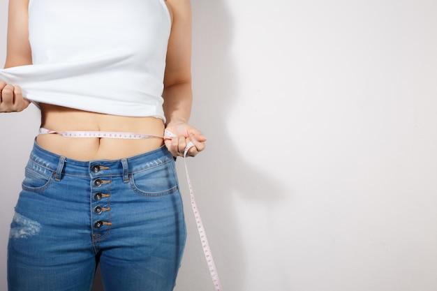 女性は彼女の腹部を測定