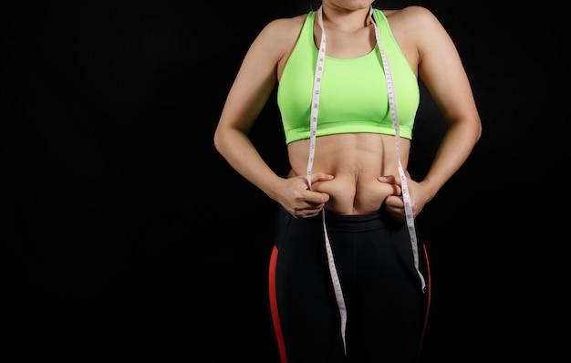 暗い背景に分離された過度の腹脂肪を持つ女性の手