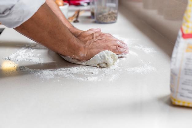 パン、パスタ、またはピザを焼くための新鮮な生地を練っているシェフ。