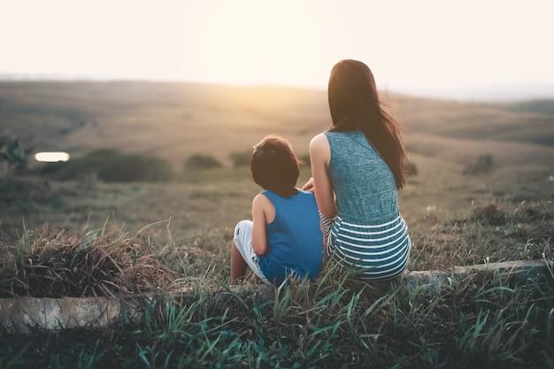 母と息子が地平線に夕日を見て