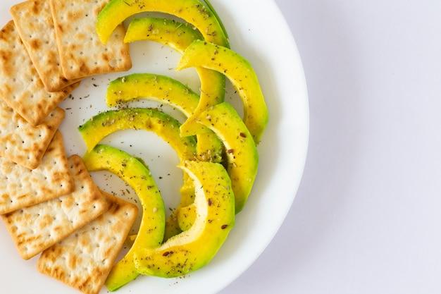 Здоровая закуска, зеленый авокадо и хрустящее печенье из цельного зерна