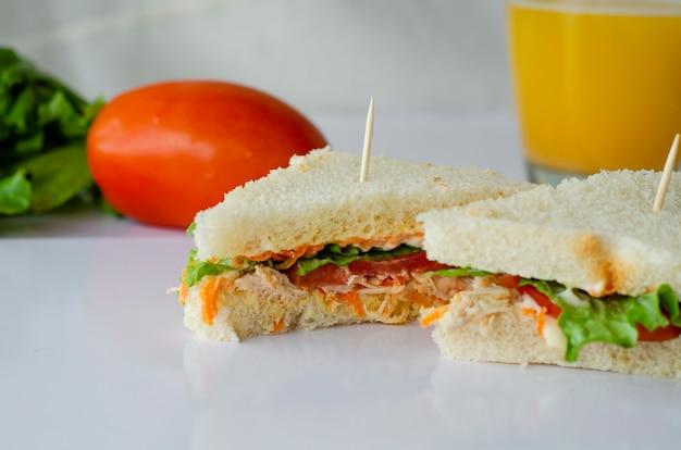 三角形の自然サンドイッチと白い背景の上のオレンジジュース