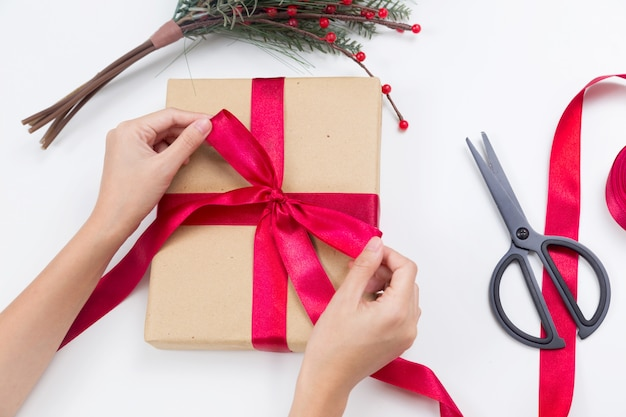Человек оборачивает рождественский подарок в крафт-бумагу с красной лентой
