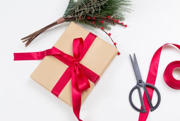 Рождественский подарок в крафт-бумаге и ножницах