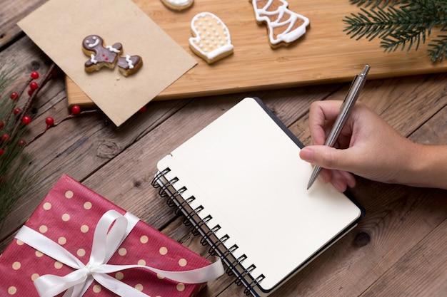 Человек, пишущий на открытой тетради с подарочной коробкой и вкусным рождественским домашним печеньем