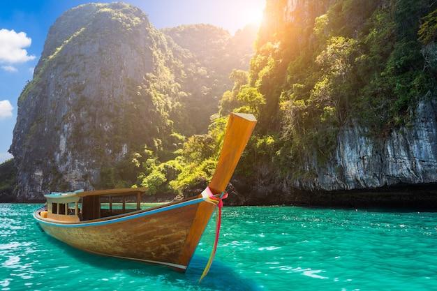 タイのクラビの熱帯海に長い尾のボートボート、日没と山