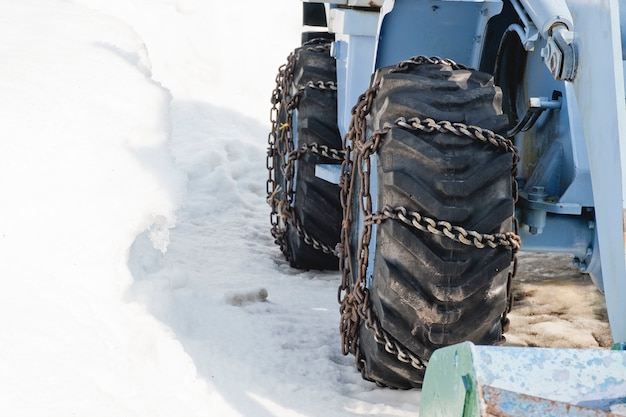トラクターは雪から吹雪に至る道を走り、清掃する