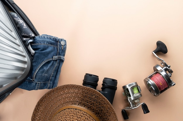 双眼鏡、帽子、ジーンズ、釣りのための回転と砂浜のフラットレイアウトのグレーのスーツケース。旅行のコンセプト
