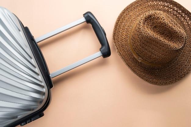 茶色の帽子とフラットレイアウトグレーのスーツケース。旅行の概念