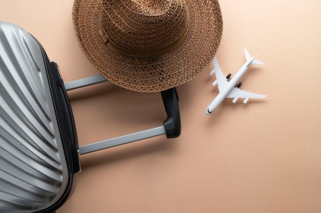 茶色の帽子とミニ飛行機とフラットレイアウトグレースーツケース
