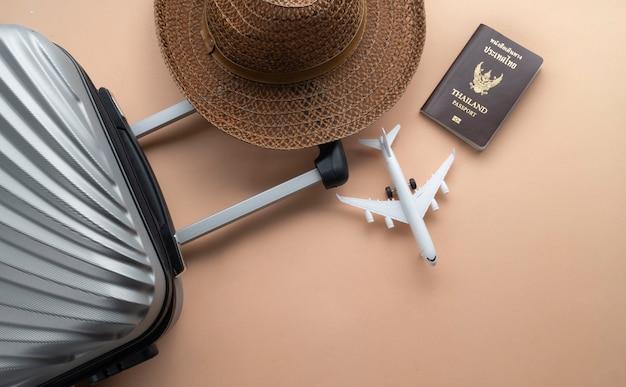 茶色の帽子、ミニ飛行機、タイのパスポートとフラットレイアウトグレースーツケース