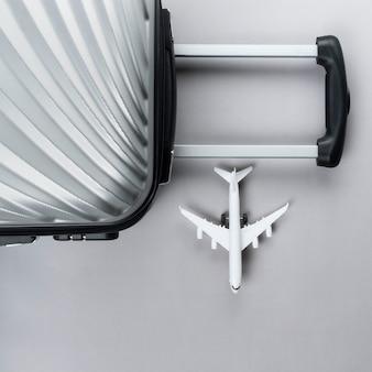 Плоский лежал серый чемоданчик с мини самолетом. концепция путешествия