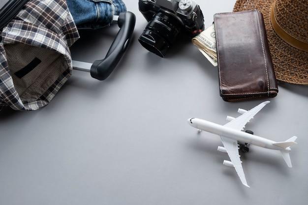 Серый чемодан для путешествий с минимальным самолетом, одеждой и аксессуарами - концепция путешествия