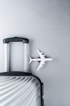 灰色のミニ飛行機とフラットレイアウトグレースーツケース