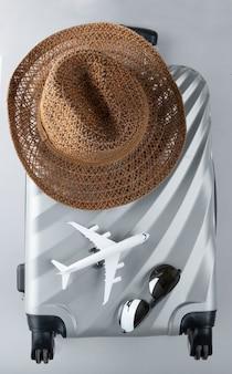 Плоский серый чемодан с мини-самолетом и шляпкой от солнца на сером фоне