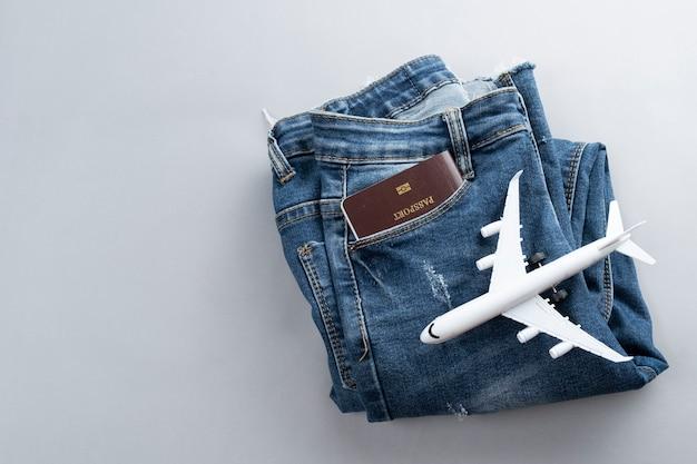 Плоский лежал мини-самолет и аксессуары для путешественников на сером фоне