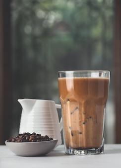 Ледяной кофе с кофейными зернами и естественным фоном