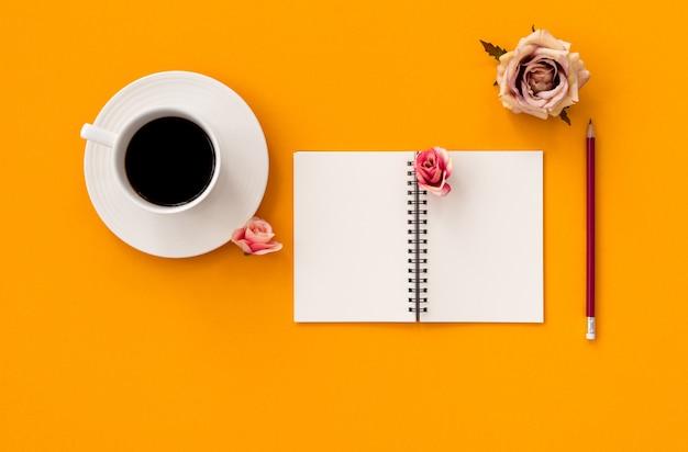 コーヒーと黄色の背景に鉛筆でメモ