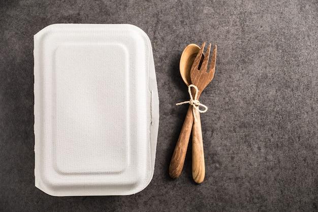 Бумажная коробка для еды с ложкой и вилкой из дерева на фоне старого мрамора