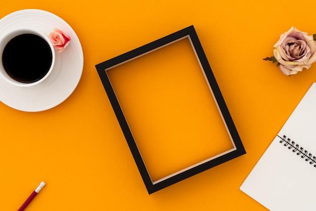 コーヒーと額縁の背景を持つスペースオレンジヴィンテージノートブック