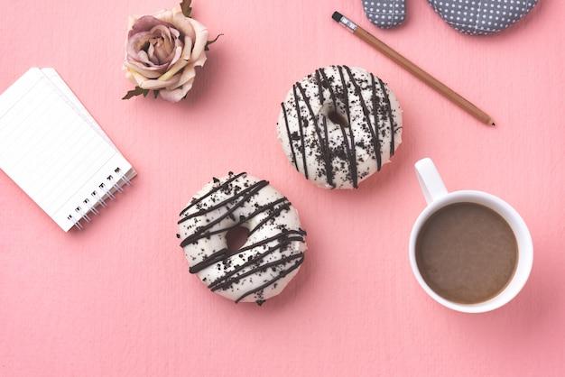 ピンクの背景の上にコーヒーとスペースドーナツ