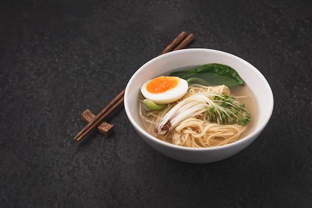 アジアのスープ麺(ラーメン)と卵の暗い背景