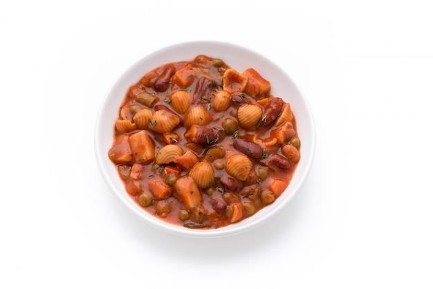 孤立した白い背景の上のトマトソースのパスタ野菜穀物エンドウ豆のスープ
