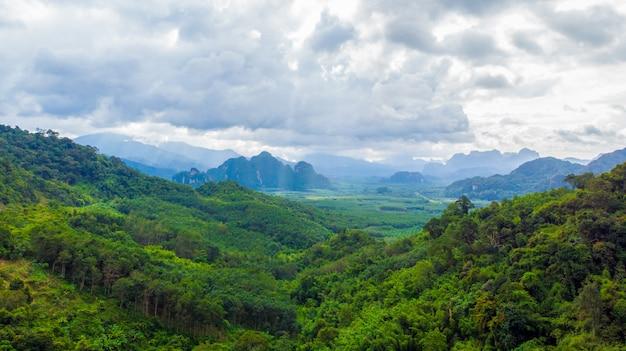 Извилистая дорога в горной долине на закате. вид с воздуха дороги асфальта в таиланде. вид сверху проезжей части, горы, зеленый лес, голубое небо и солнечный свет