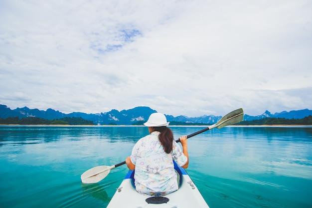 女性と一緒にカヤックとカヌーを旅行します。山を見る