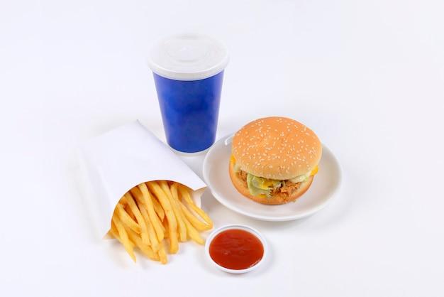 ハンバーガー、フレンチフライ、および白い背景で隔離されたソフトドリンクを含むファーストフードセット。