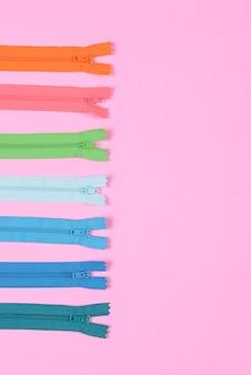 ピンクの背景に縫製のためのカラージッパーのフラットなレイアウト、縫製と針のコンセプト。