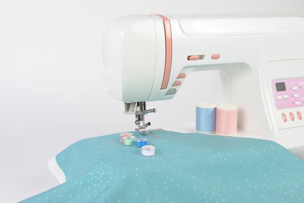 ミシンとカラフルなスレッドロール、はさみ、布と縫製のためのアクセサリー。