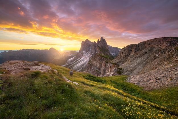 イタリアドロミテから日の出の朝に金色の空と緑の山の素晴らしい風景を見る。