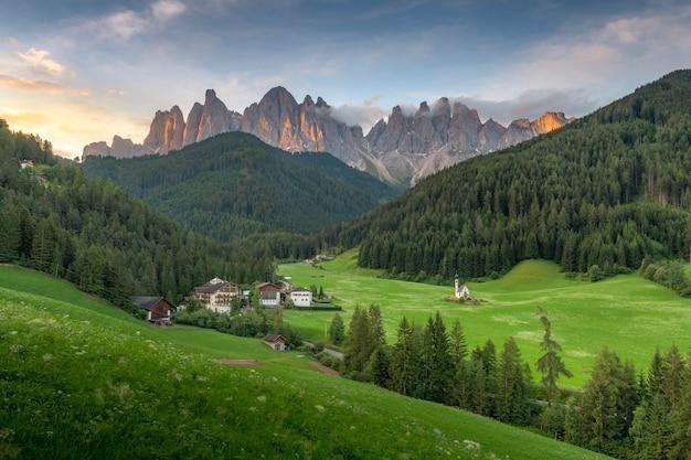 イタリアのドロミテから日の出の朝に緑の丘と青い空と山の素晴らしい風景を見る。