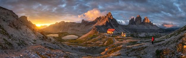 家とイタリア、ドロミテ、トレチメから夕日に金の空と山の風景パノラマビュー。