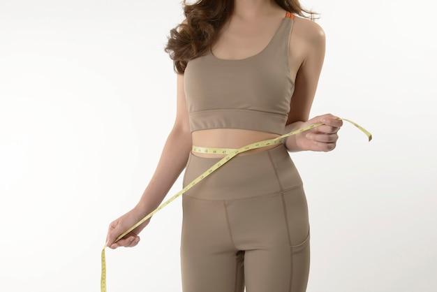 Стройная молодая азиатская женщина измеряет свое тело на белом