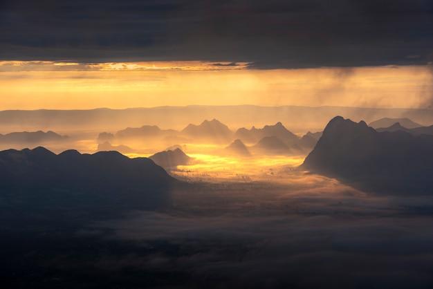 山の霧と朝日の出。日の出