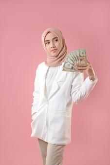 若いイスラム教徒の女性はお金を保持します。