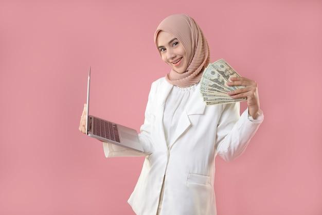 Молодая мусульманка держит деньги и ноутбук