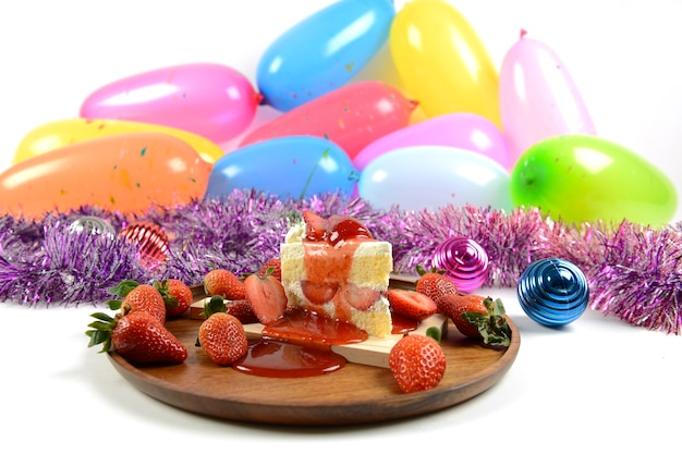 特別な日にお祝いのためのパーティー風船の背景にストロベリーケーキ。
