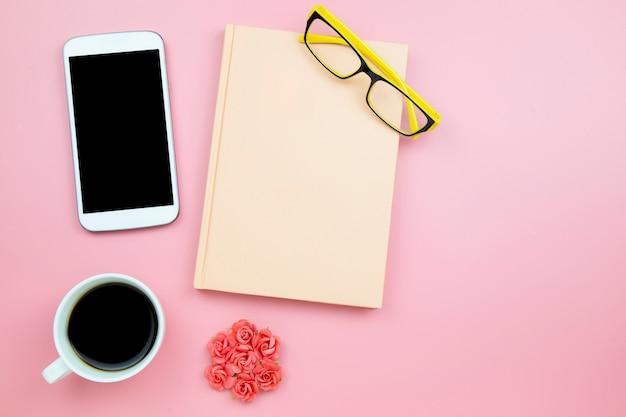 ノートパソコンの携帯電話の黒いコーヒーの花は、ピンクの背景に黄色のメガネをバラ