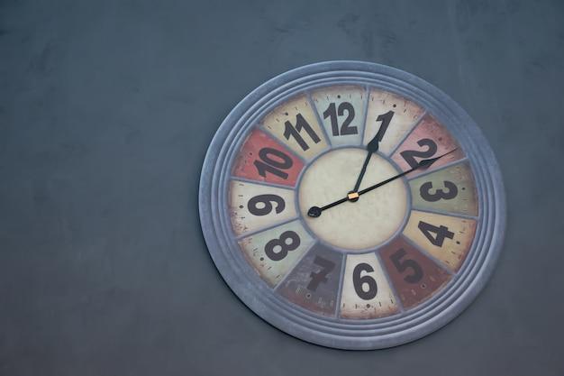 壁のビンテージトーンに掛かっているモダンな壁時計。