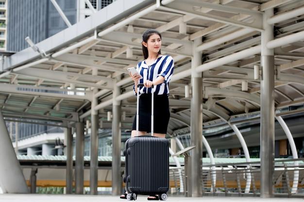 ビジネスセンターでのスーツケース付きのビジネス女性