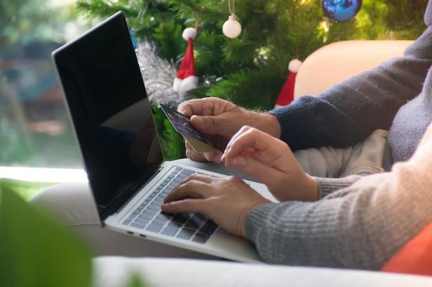 クレジットカードとラップトップを使用してオンラインショッピングをするカップル