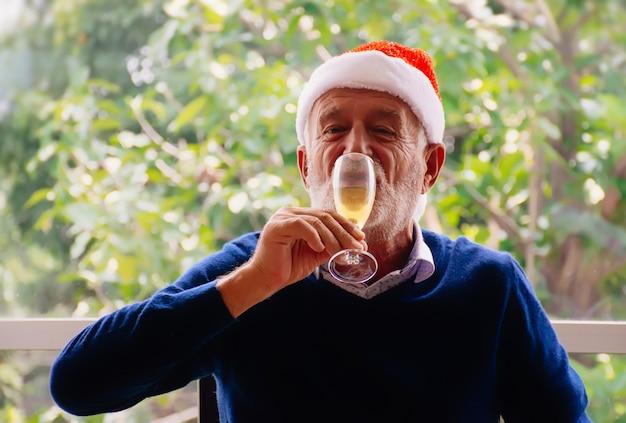 Старший мужчина пьет вино.
